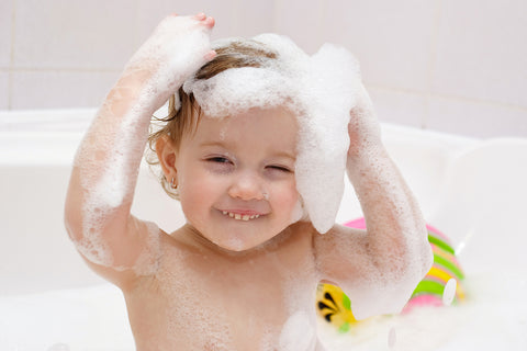 baby having fun with bubbles during bath time