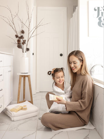 Mom showing daughter what products she uses during bath time