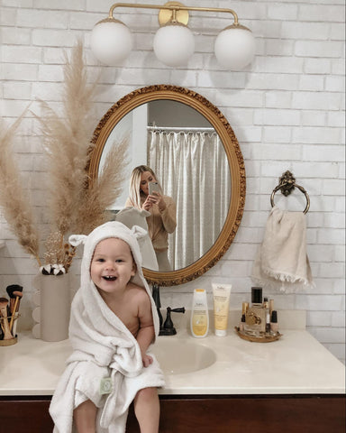 Mom taking picture of baby in robe after bath time