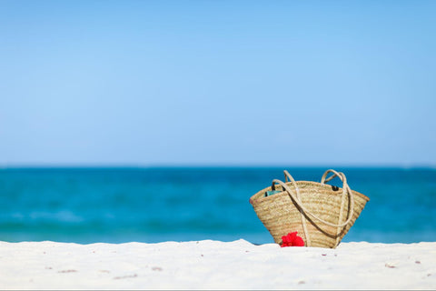 Bag on beach filled with beach packing list essentials