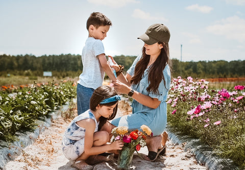 Mom applying skin care products with calendula benefits on her kids