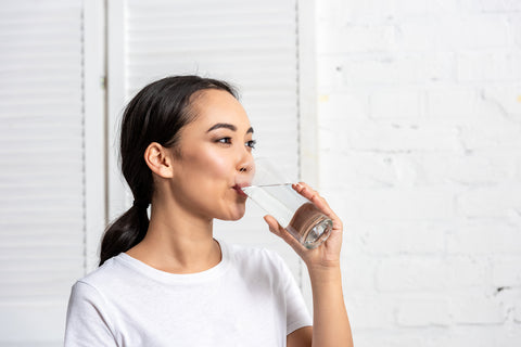 woman drinking water to hydrate herself