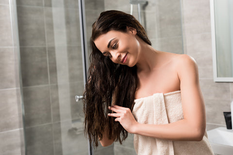 woman detangling hair after washing with chemical-free shampoo
