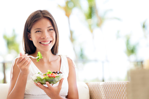 Woman eating a salad to help prevent dry skin