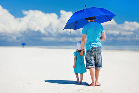 Dad and child using an umbrella to protect their skin from the sun