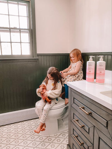 Young girl brushing sisters frizzy hair