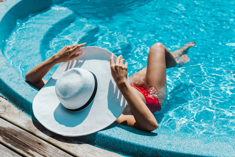 woman in pool wearing hat as part of hair care for swimmers