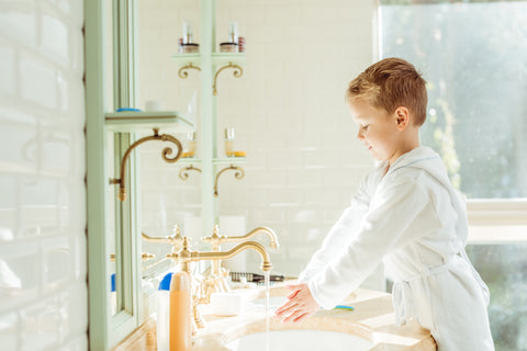 Boy in bathroom washing his hands