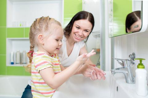 mom and daughter washing hands together
