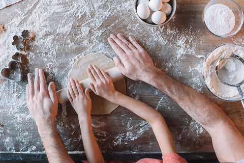 hands of family rolling dough together