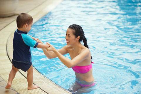 mom helping kid to get into the pool