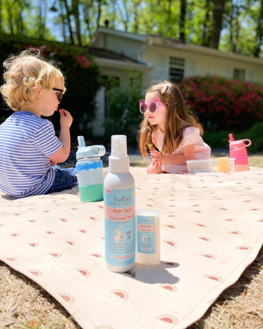 Two kids having a picnic outside set up with all the sun protection essentials