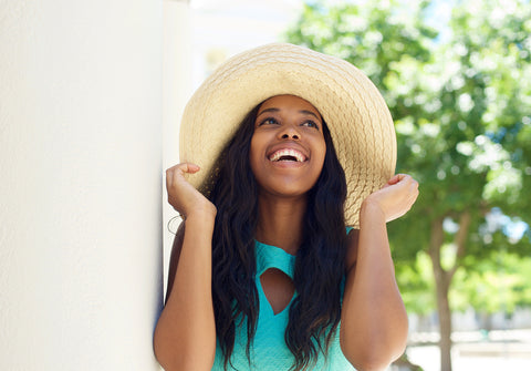 Woman wearing hat wondering how much sunscreen to use on face