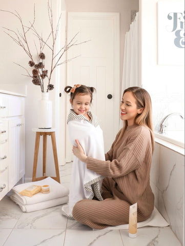 Mom drying off daughter after taking show and washing hair with chlorine shampoo