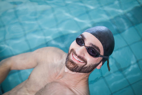 Man swimming with swimmers cap to prevent chlorinated hair