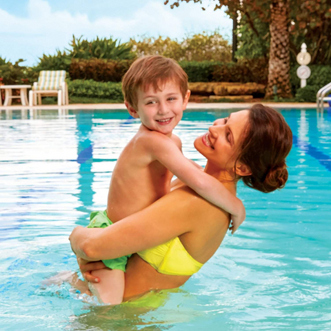 Woman with child in pool think about how to get chlorine out of hair
