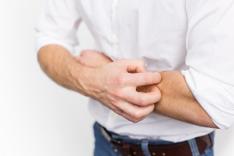 man itching his arm wishing he knew how to hydrate skin