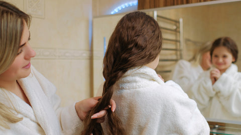 Mom braiding daughters hair teaching her how to moisturize hair