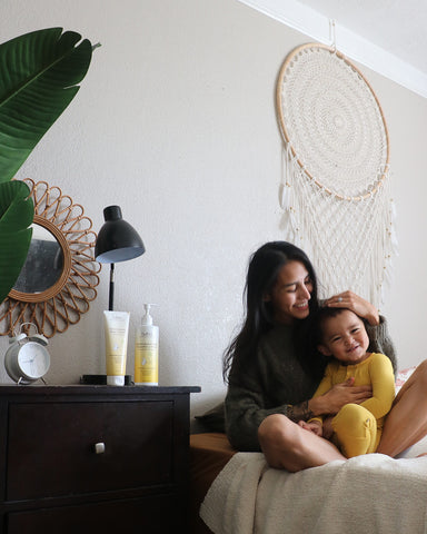 Mom with child on bed with large dream catcher on wall
