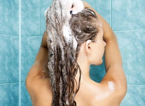 Woman washing hair wondering how to use conditioner properly
