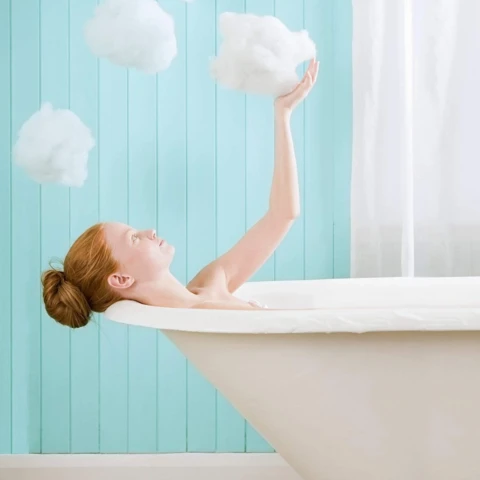 Woman in bathtub wondering how to use conditioner