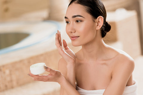 Woman applying Hyaluronic acid skin care products to face