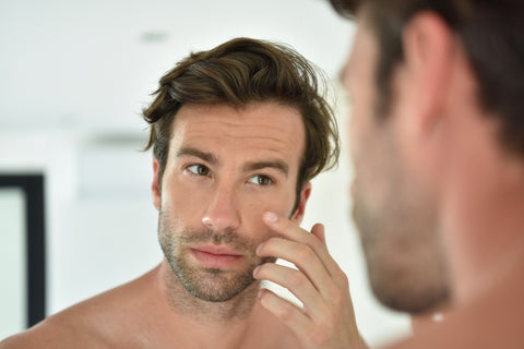 Man who uses hyaluronic acid is checking his skin in the mirror