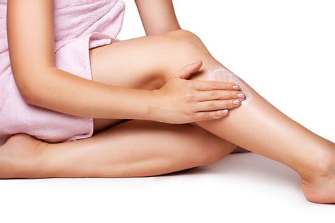 Woman applying  lotion on legs to relieve itchy skin