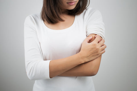 Woman scratching itchy skin on arm