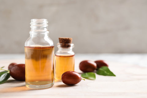 jojoba oil in a bottle with seeds next to it