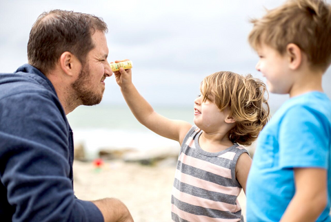 kid applying coral reef safe sunscreen on dad