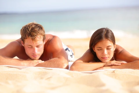 Couple on the beach protecting their skin with mineral sunscreen