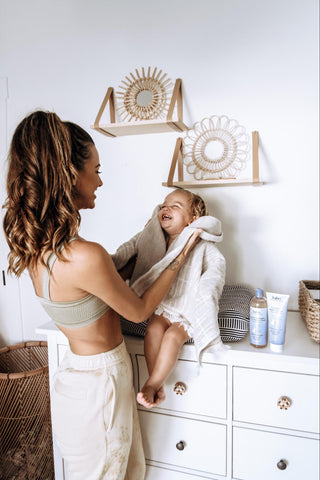 Woman drying off child after bath time