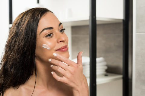 Woman applying miracle cream on face