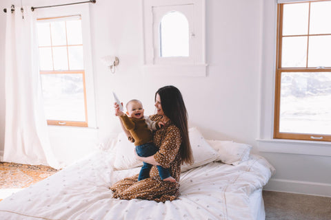 Woman holding baby on bed
