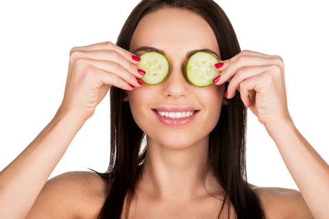 woman holding cucumbers on eyes