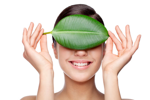 woman holding leaf over eyes and forehead