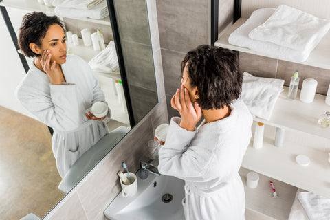 woman in bathroom using natural skin care