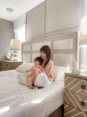 Mom holding baby on bed