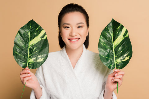woman holding two large leaves