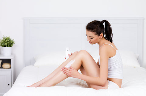woman applying lotion on legs to prevent eczema