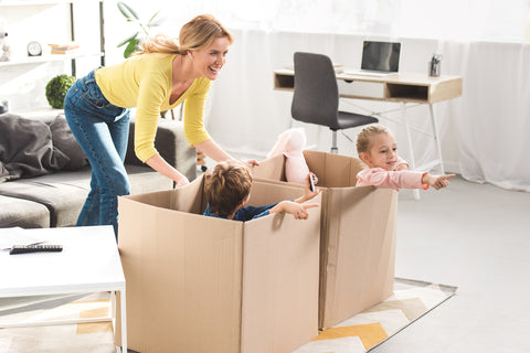 family playing with boxes making recycling for kids fun