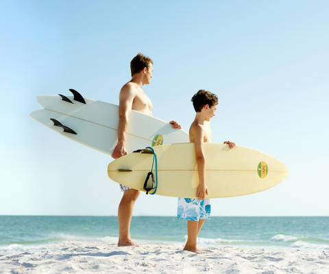Father and son at the beach holding surf boards