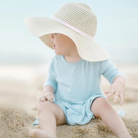 Baby wearing a hat at the beach to protect her skin