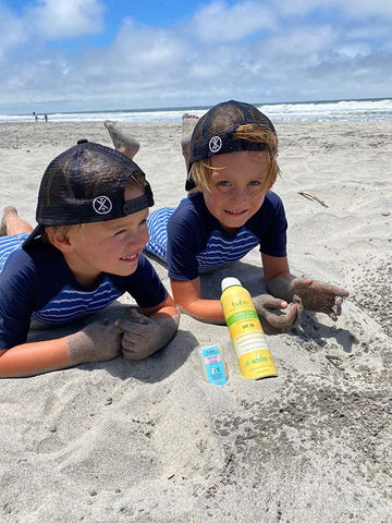 Two kids at the beach with Babo Botanicals Sunscreen