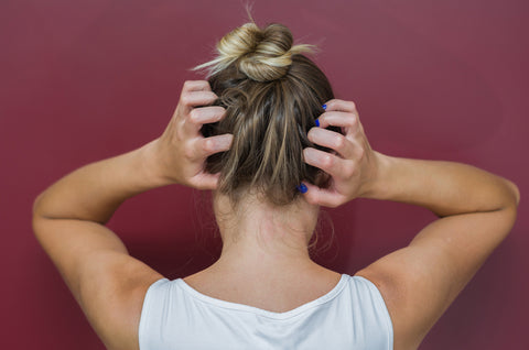 Woman with a bun itching her head