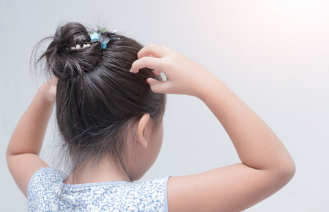 young kid itching her sensitive scalp
