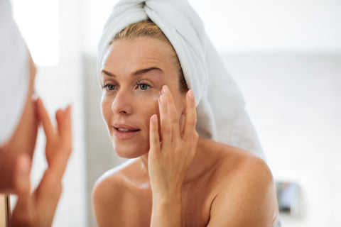 Woman fresh out of the shower applying face cream with shea butter