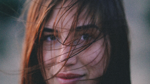 Woman with soft hair flowing across her face in the wind