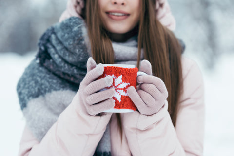 Woman in snow holding coffee wearing gloves to protect her soft hands